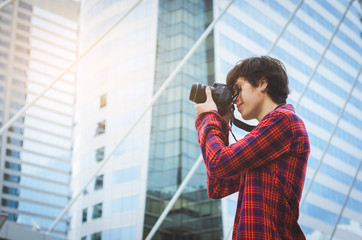 handsome young caucasion man take photo with digital camera take photograph in the metropolis against high building windows background on holiday. tourism, travel concept.