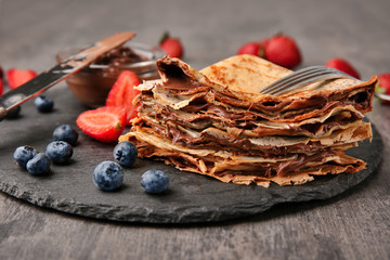 Slate plate with thin pancakes, chocolate paste and berries on table