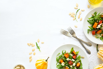 Fresh autumn salad with baked pumkin, arugula, cheese and seeds on white table cloth. Space for copy