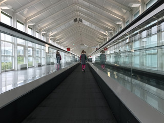 Lonely cute child travelling on travelator at airport terminal