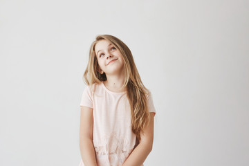 Beautiful light-haired girl in pink dress looking upside with foxy face expression, thinking about lying about marks in school to get candies from mother.