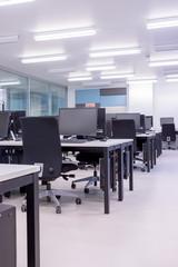 Leeres Großrambüro, Computer, Schreibtische und Drehstühle