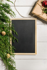Fir branches border and black chalk board on white wooden background, good for christmas backdrop