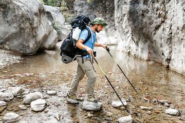 Backpacker man wading small mountain river in Goynuk canyon, lycian way, Turkey