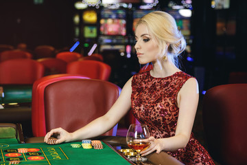 Young blonde woman playing roulette in the casino