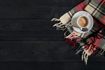 White cup of the coffee and vintage scarf on black wooden background