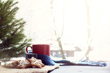 atmosphere of home comfort/ festive figured cookie under the tree, next to a red mug in scarf on the background of a winter landscape outside the window