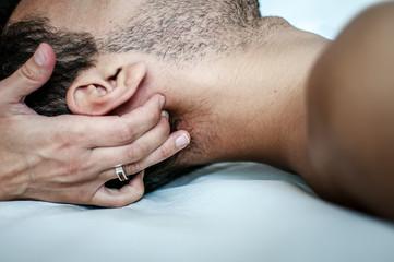 fisioterapista massaggia giovane paziente per curare un dolore cervicale