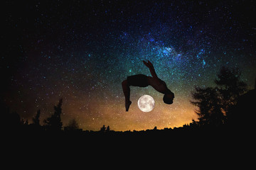 sporty man jumping silhouette at the night starry sky and moon background.