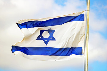 Israel flag close up shot on a background of blue sky. White and blue colors. Israel flag waving against sky