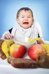 Crying unhappy Baby boy must eat healthy food for breakfast on bright blue background
