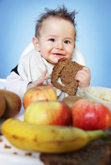 Cute Baby boy eating healthy food for breakfast on bright blue background: vertical