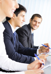 Three happy smiling businesspeople at meeting