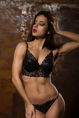 Sensual brunette model with athletic body in sexy lingerie posing at studio