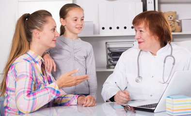 Medical worker talking with mother and daughte