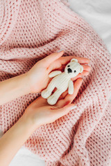 A woman is holding a knitted baby bear toy
