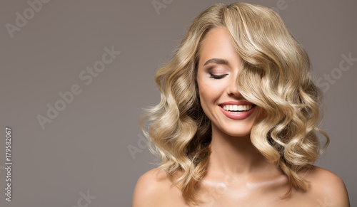 Wall mural Blonde woman with curly beautiful hair smiling on gray background.