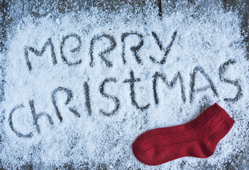 Merry christmas hand drawn lettering with red sock on wooden board