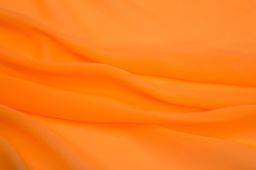 bright orange fabric lined with soft folds, artificial silk
