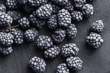 Frozen blackberry on black slate. Close up. Top view. High resolution product.