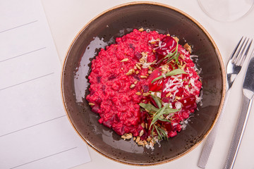 Orzotto with beet, goat cheese and pine nuts, rosemary, cheese parmesan