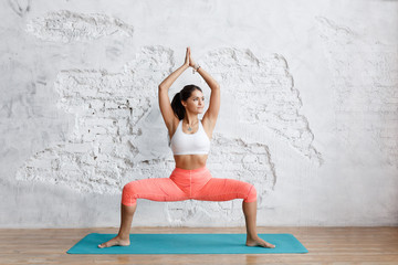 Beautiful Yoga: A pose of the goddess.The portrait of the beautiful young woman, works against a white brick wall, doing yogas or Pilates of exercise. Standing in card Sumo, create the goddess.