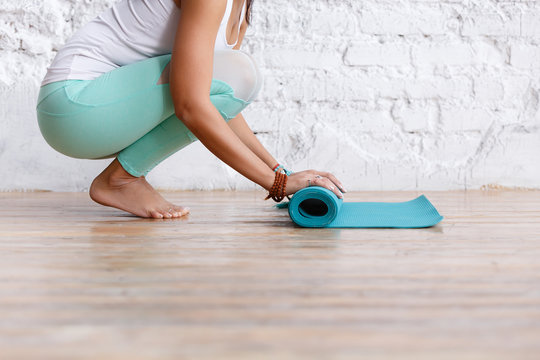 Close-up of attractive young woman folding blue yoga or fitness mat after working out at home in living room. Healthy life, keep fit concepts. Horizontal shot. white loft studio
