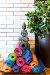 Pile of colorful yoga mats forming Christmas tree with Buddha figure on top