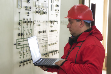 Technician with laptop reading instruments in power plant control center