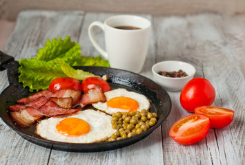 Breakfast, fried eggs with bacon and tomatoes in a frying pan. Morning coffee. Menu for a cafe, the concept of the morning.