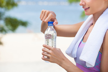 A sportswoman holds a bottle of water in her hand during a sports training session.