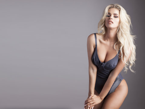 Sexy blonde in grey body isolated on grey background.