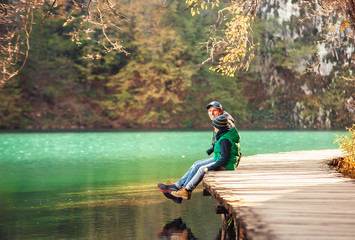 Father and son sit on wooden bridge over the lake