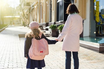 Mother taking child to school. Holding hands, background - autumn city.