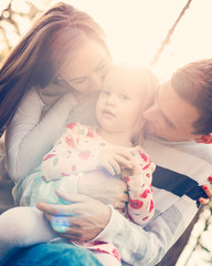 Young family of three having fun in a park enjoying their time together. Real people, real family, authenticity concept