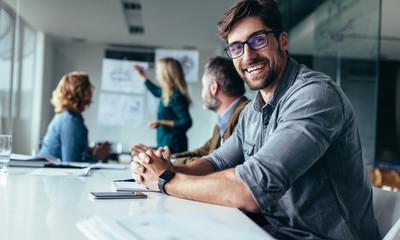 Smiling designer sitting in conference room