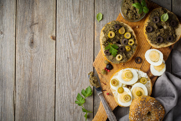 Sandwich  from bread or bagels with tapenade, olives and boiled chicken eggs on an old wooden background. Selective focus. Top view. Copy space.