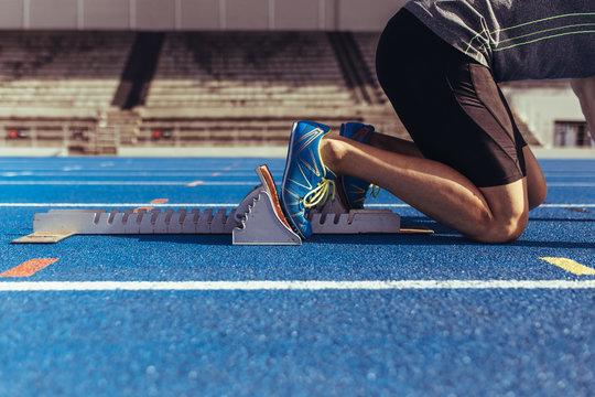 Sprinter resting his feet on starting block on running track