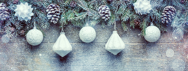 Snowy Christmas Background, Fir Tree Branches With Pine Cones And Xmas Baubles On Wooden Background, Festive Banner With Copy Space