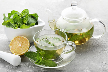 Cup of tea and teapot with mint leafs on wooden table