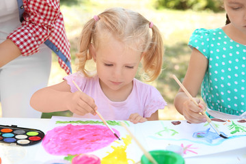 Little girl on painting lesson outdoors