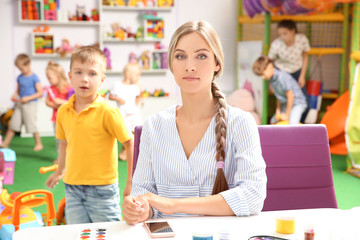 Female teacher sitting at table in playroom