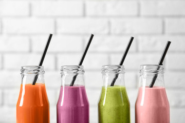 Bottles with yummy smoothie on light background