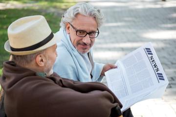 Joyful senior male friends reading newspaper