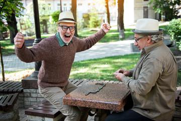 Cheerful senior pensioner winning dominoes game