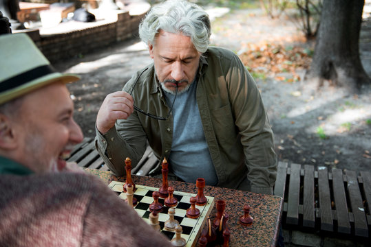 Mature male pensioner thinking about next move on chessboard