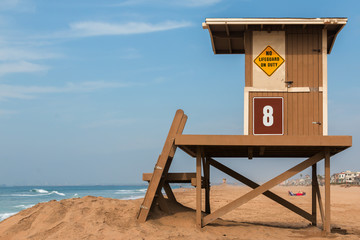 Wooden lifeguard stand on beach. No lifeguard on duty sign. Ocean waves, blue sky and clouds background..