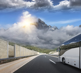 Tourist bus rushes along the country high-speed highway against the background of a mountain landscape.
