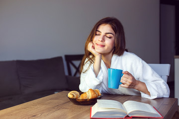 Beautiful caucasian girl in a white bathrobe enjoys morning coffee and croissant, time in the kitchen