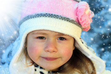 Close-up portrait of adorable smiling child girl wearing pink knitted hat in snowy winter day